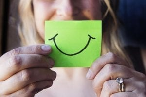 woman holding up a smiley on a green post it note