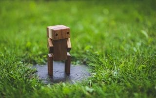 wooden robot chatbot alone on grass
