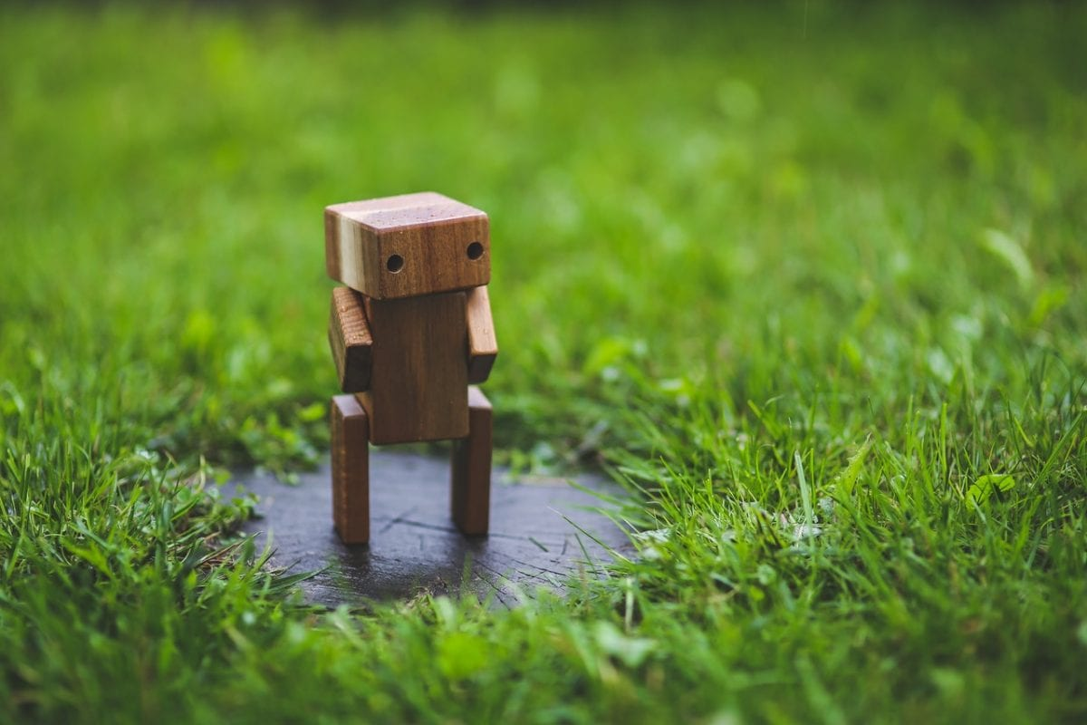 wooden robot chatbot alone on grass