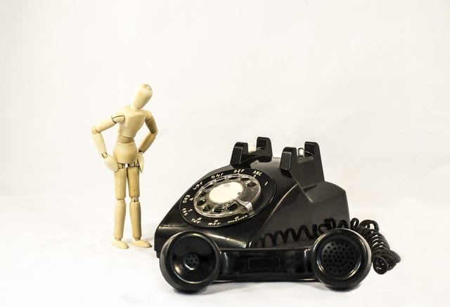 chatbots vs ivr wooden mannequin next to an old fashioned phone