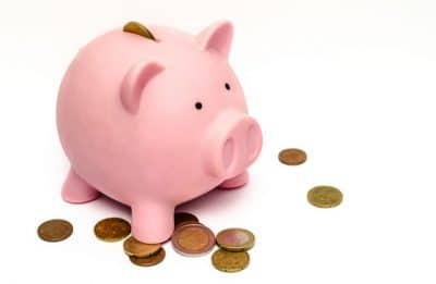 pink piggy bank with scattered coins
