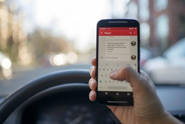 close up of smartphone being used in car free chatbot software