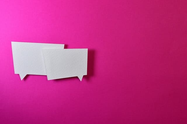 two white paper message balloons on a bright pink background