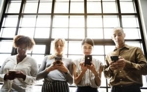 four people on smartphones in front of a glass wall